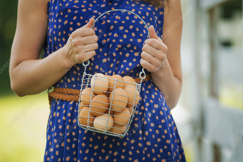 A woman holding basket of hen's eggs