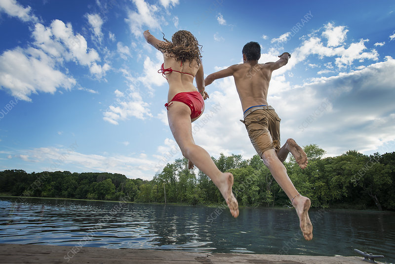 Two people jumping into a lake