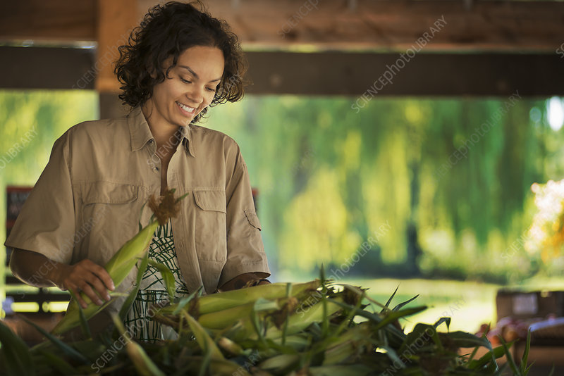 A woman with fresh corn on the cob
