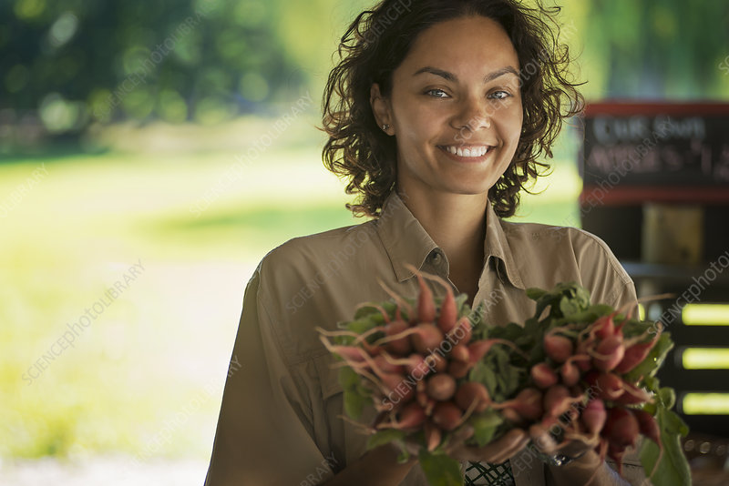 A woman carrying fresh red radishes
