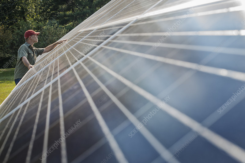 A man by a solar photovoltaic panel
