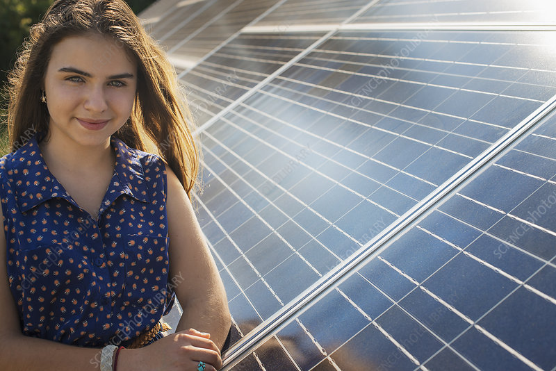 A girl standing by a solar panel