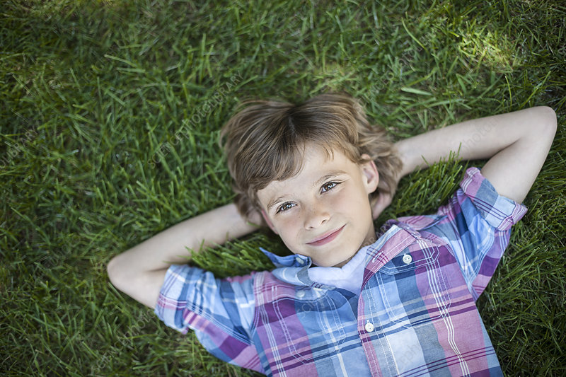 A boy lying on the grass