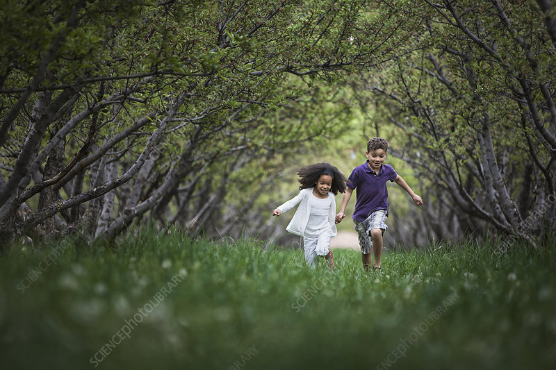 Two children running in a tunnel of trees