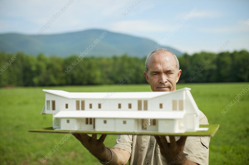 A person holding a building scale model
