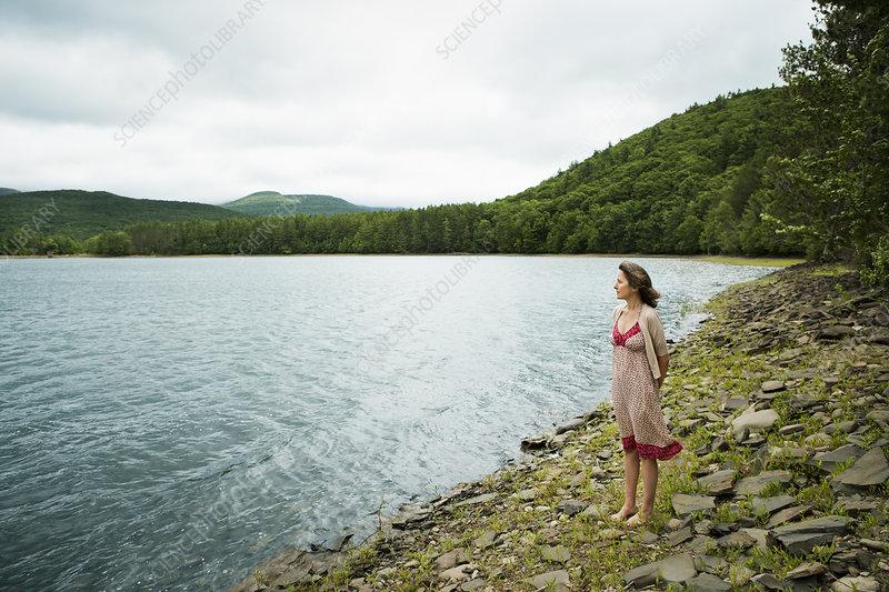 A woman by a mountain lake