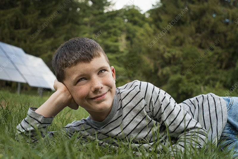 Boy outdoors beside Solar Panels