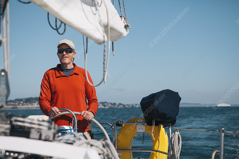 Middle aged man steering a sailboat