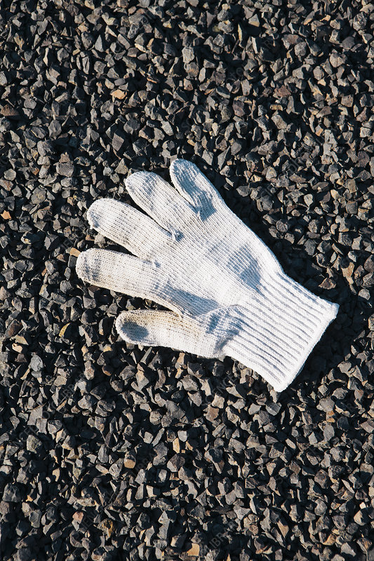 Discarded white glove on gravel