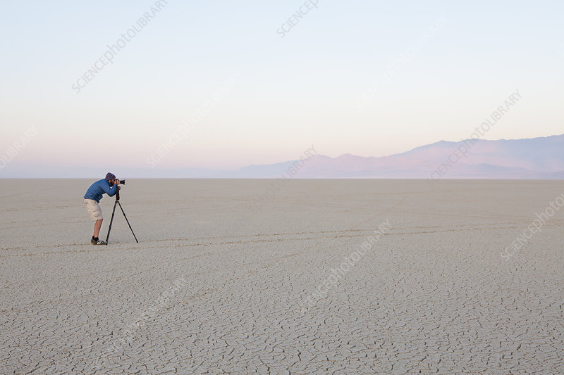 Man taking photograph in desert