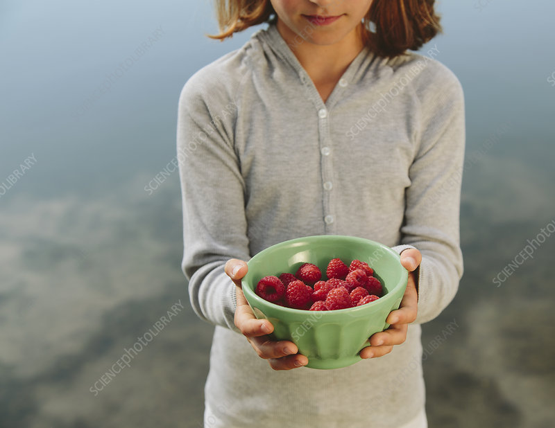 Girl with bowl of organic raspberries