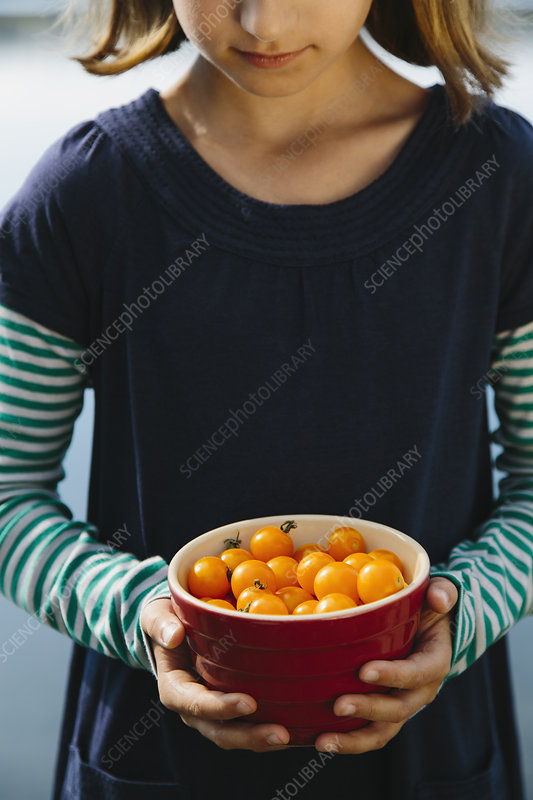A girl holding a bowl of cherries