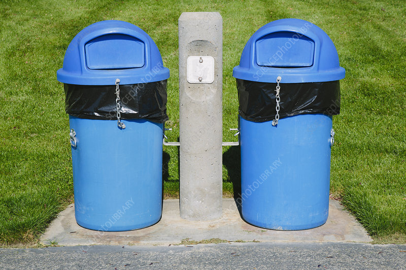 Blue trash cans by grassy field