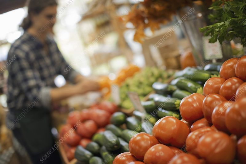 Young man arranging food on a farm stand