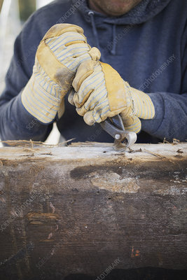 A man removing nails on recycled wood
