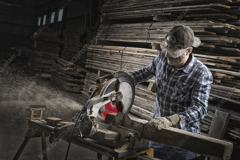 A man in goggles cutting timber with saw