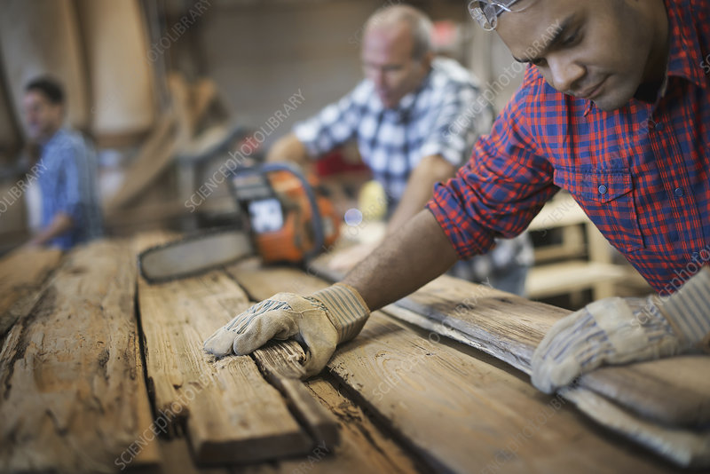 A man measuring planks of wood.