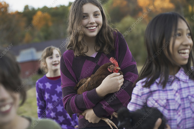 Two girls holding chickens, on a farm.