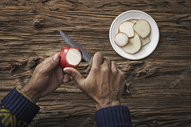 A person slicing a red skinned apple.
