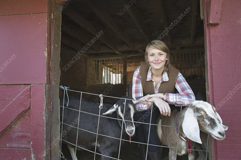 A young girl with two goats