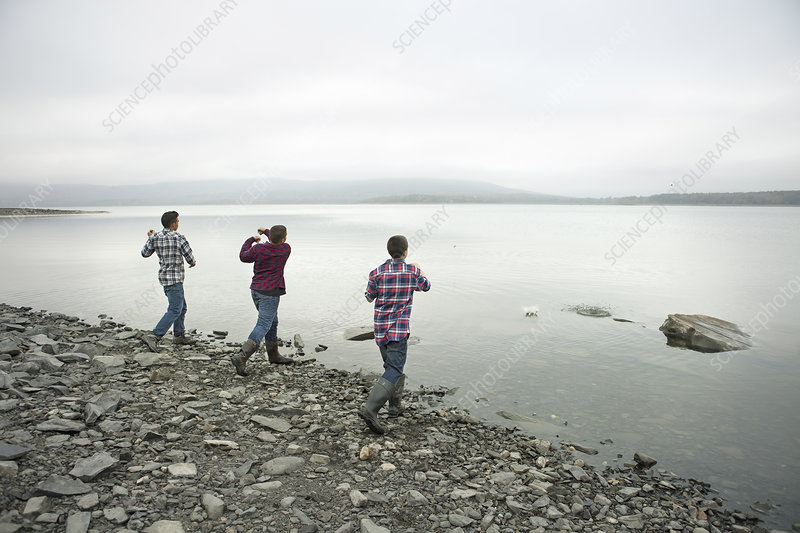 Boys throwing skimmers pebbles on a lake