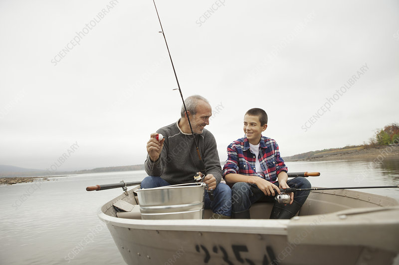 A man and a boy fishing from the boat.
