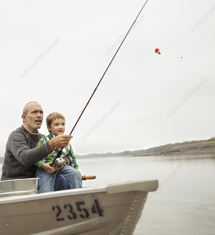 A man showing a young boy how to fish