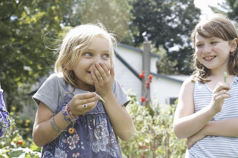 Two children in a garden laughing.