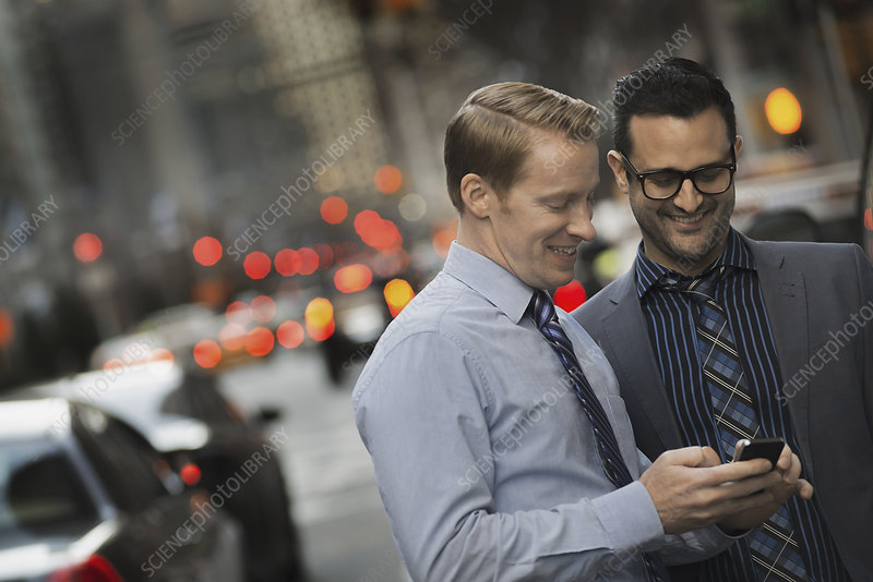 Two men checking a cell phone display
