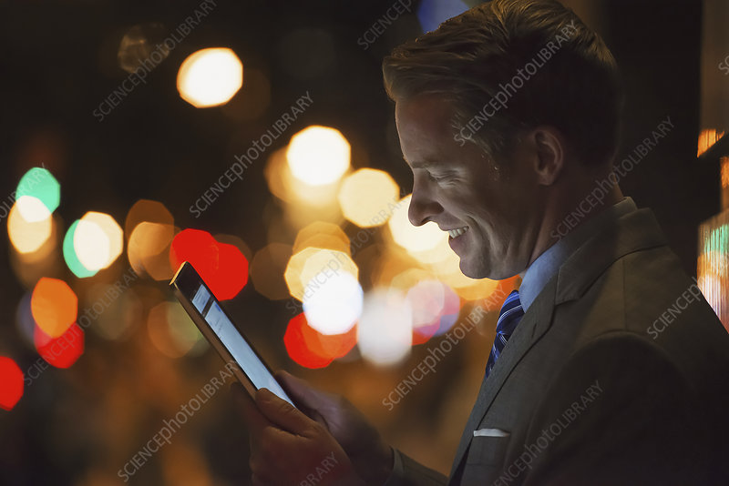A man in a city using a tablet.
