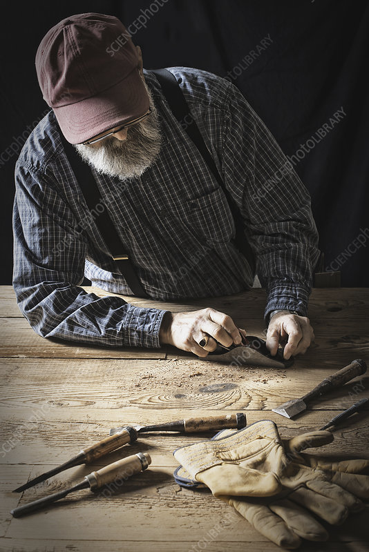 A man sanding knotted uneven wood.