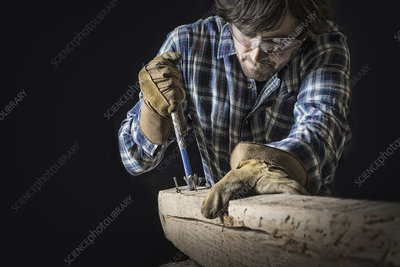 A man extracting nails from wood plank