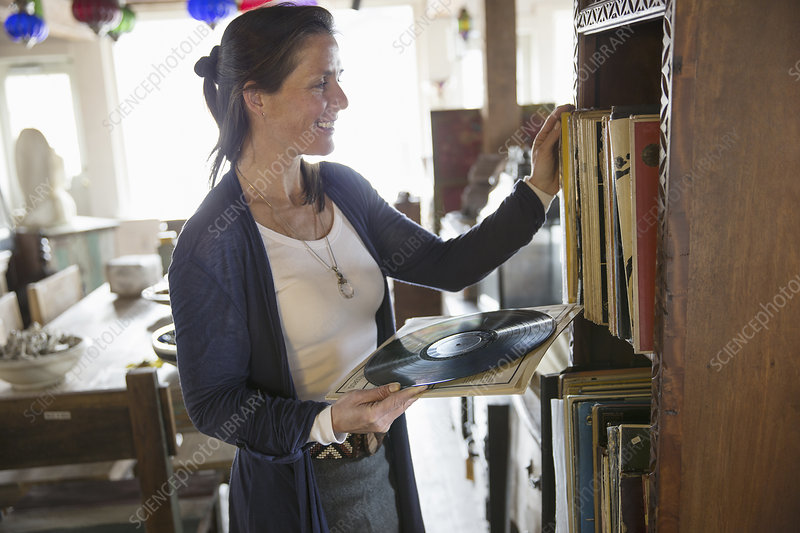 A woman in a store holding vinyl records