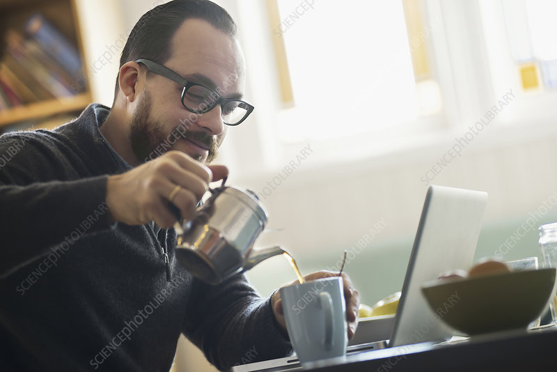 A bearded man having a drink of coffee.
