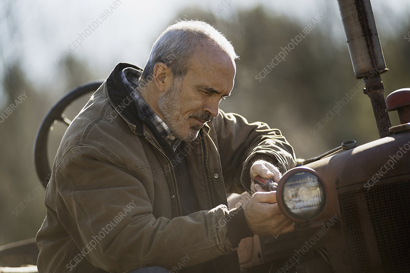 A man in a jacket working on a tractor.