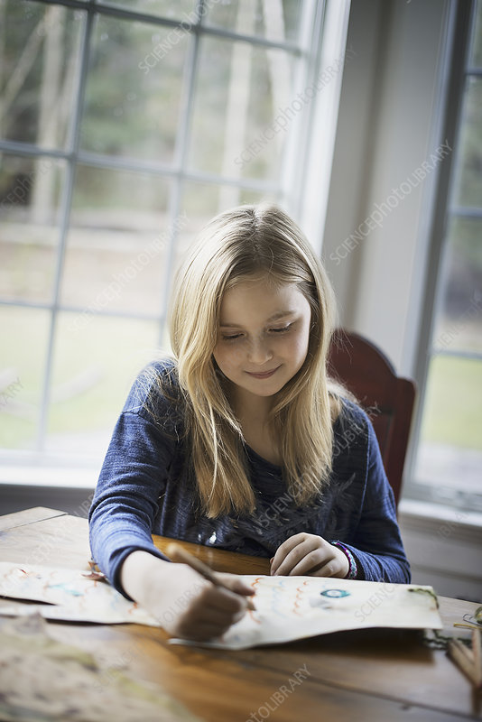 A young girl sitting at a table drawing