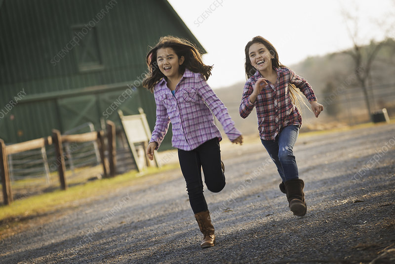 Two children running by a farm building
