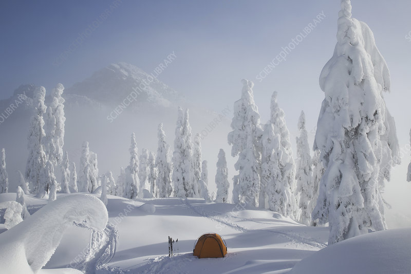 Orange tent on a mountain ridge in snow