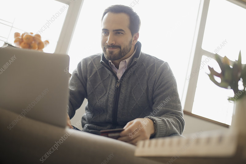 A man on-line shopping on a laptop