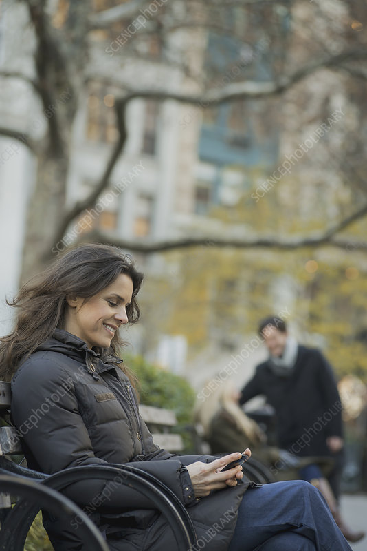 Woman seated in a park with smartphone