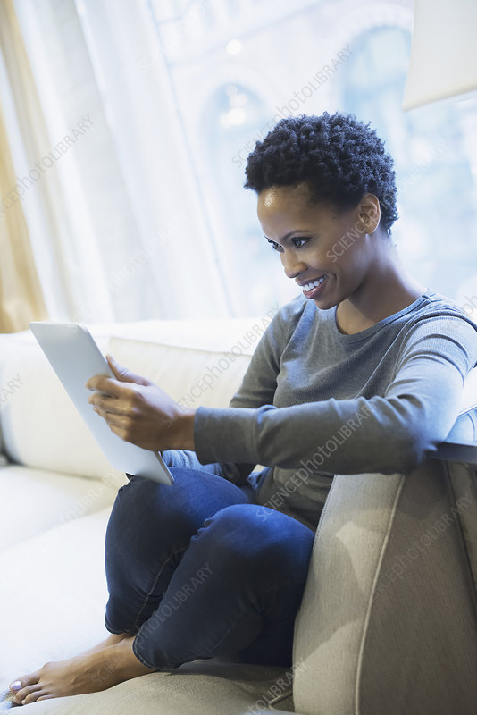 Woman relaxing at home with tablet
