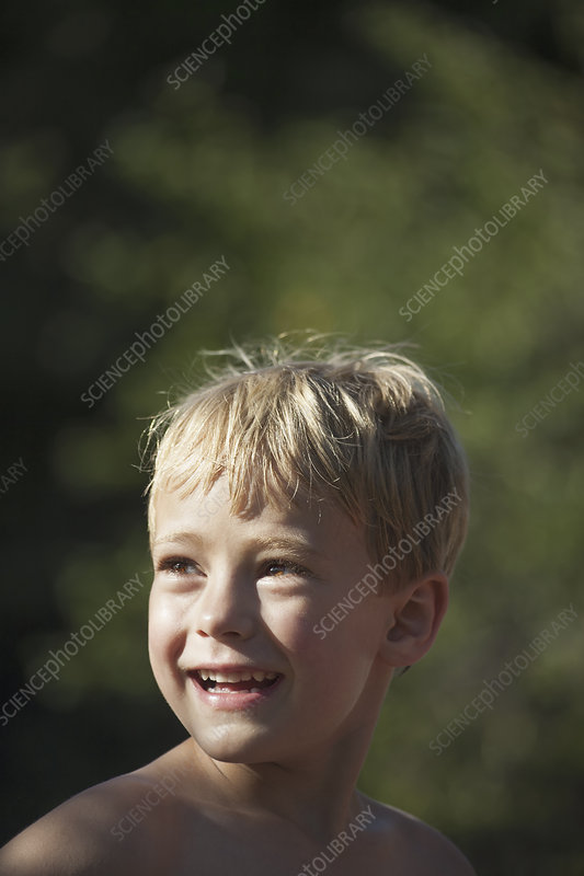 A child turning his head smiling.