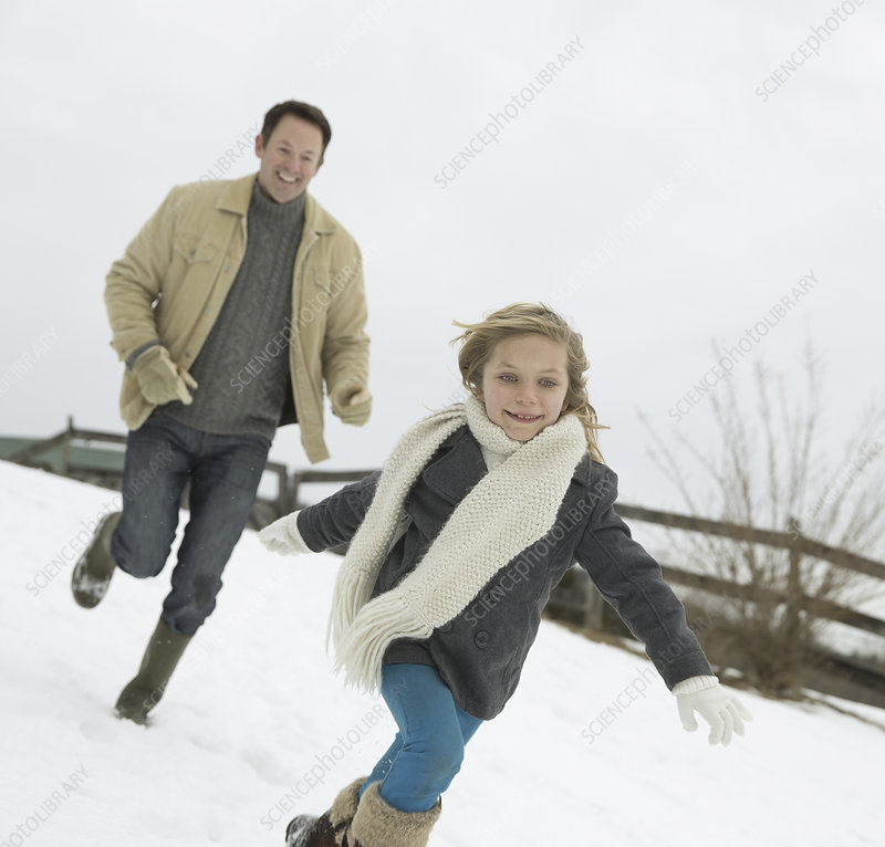 A man chasing a young girl in the snow