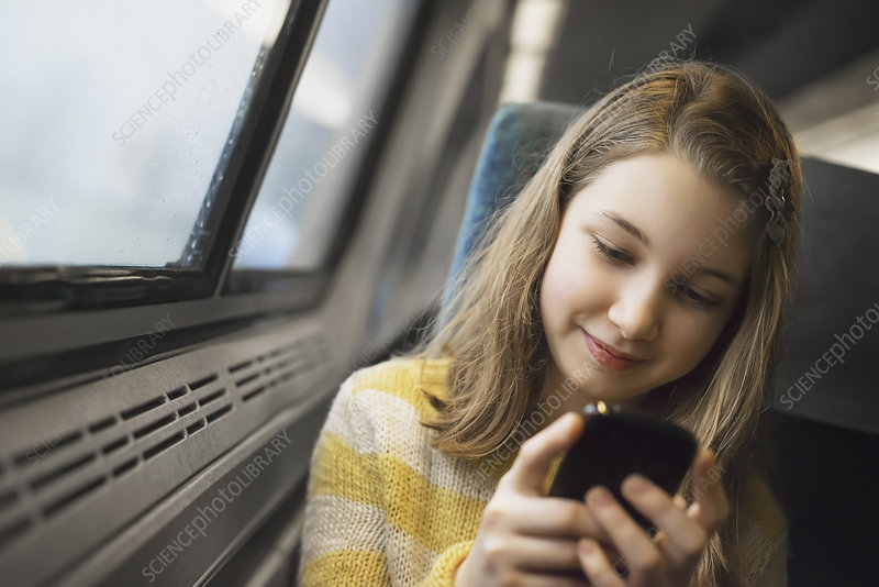 A girl by train window using mobile phone