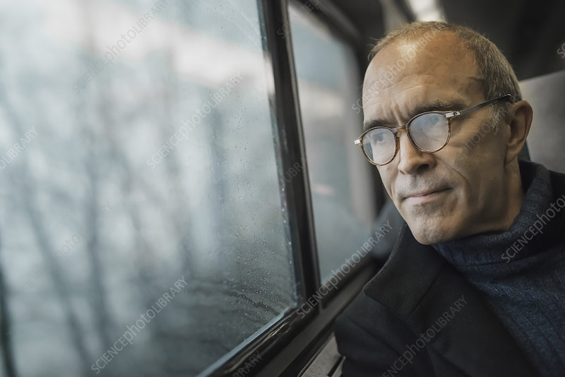 A mature man in a window seat on a train