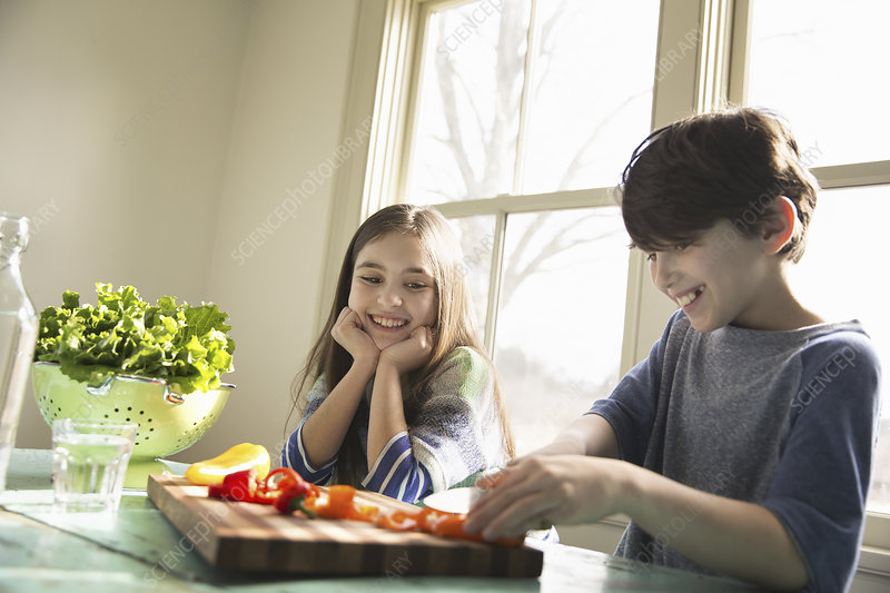 Two children chopping bell peppers
