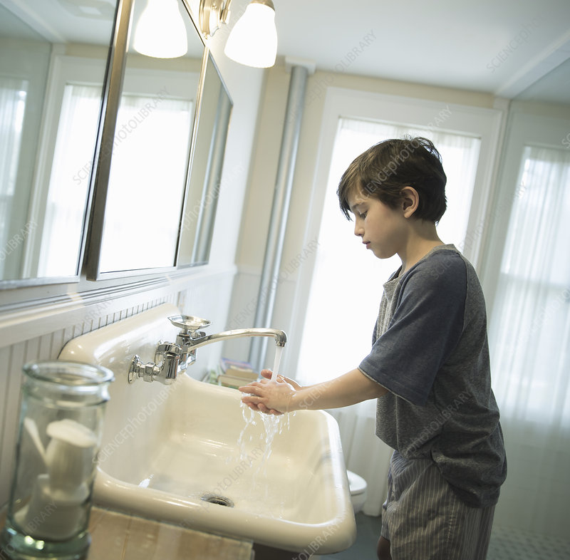 A boy washing his hands under the tap