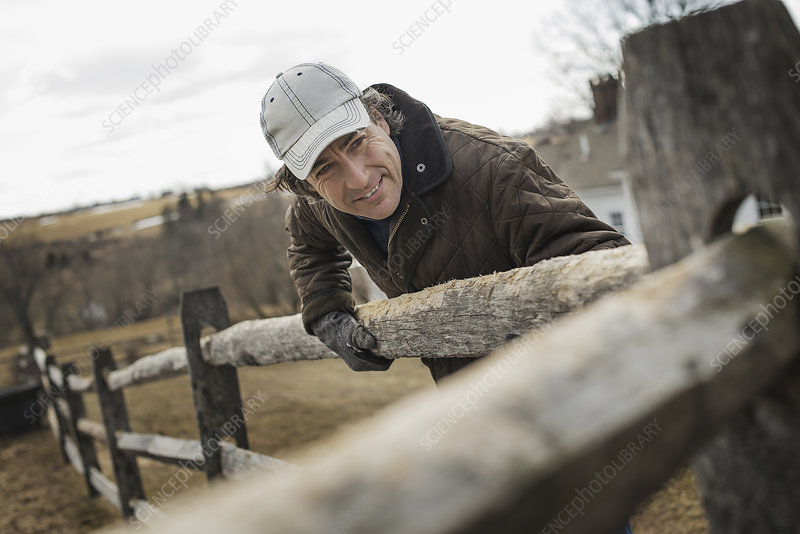 A man by a farm post and rail fence