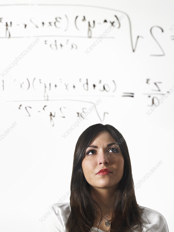 Woman writing a mathematical equation