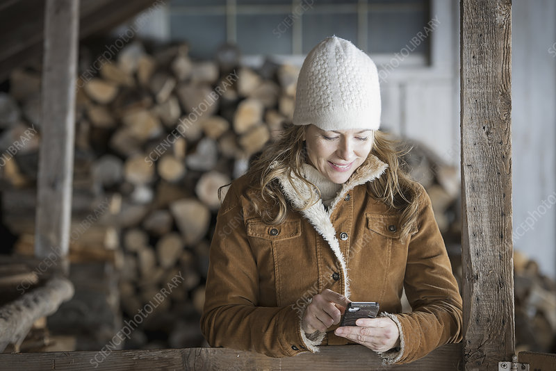 A woman in sheepskin using a cell phone.